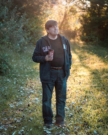 Tanner Elton stood in morning sunlight on the property with a cup of coffee